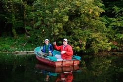 Two men with fishing rods in a boat against the backdrop of beautiful nature and the river at sunset fish