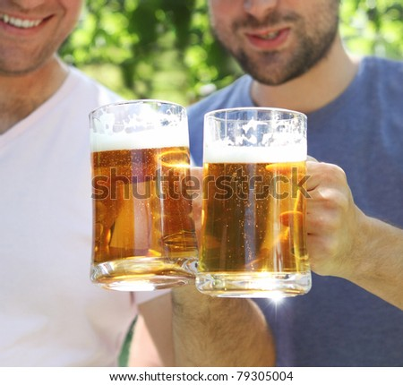 Two men with glasses of the light beer in the garden - stock photo