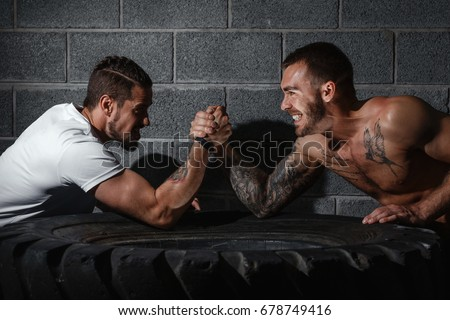 Two men with hands clasped in arm wrestling challenge. Bodybuilding concept