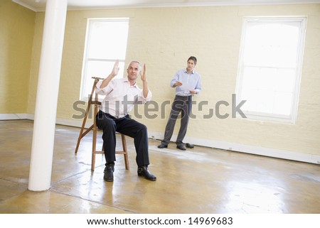 Two men with ladder in empty space making plans for room - stock photo