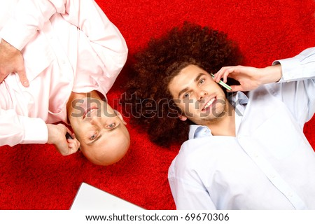 Two men with phones to their ears, laying on their backs in opposite directions on a bright red rug with a pad of paper beside them.  Shot taken from directly above them.