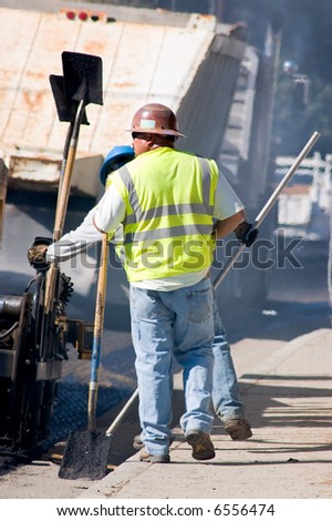 Two men working on a road repaving project.