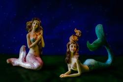 Two mermaids at night.