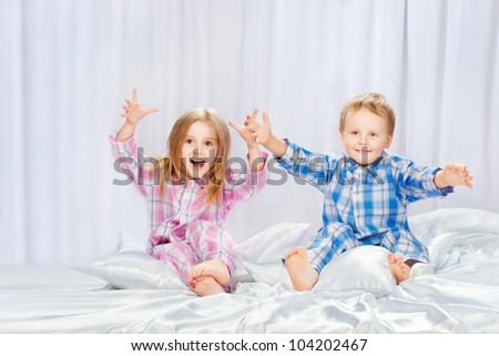 Two merry children playing on the bed