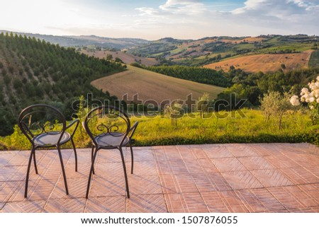 Two metal chairs on a terrace overseeing cropped fields in the european countryside. Wineyards and other crops on the back. Freedom, tranquility, peaceful, calm concepts.  #1507876055