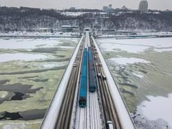 Two metro trains on Kiev bridge across the frozen Dnieper river. Textured pattern on ice. Aerial drone view. Winter frosty morning.