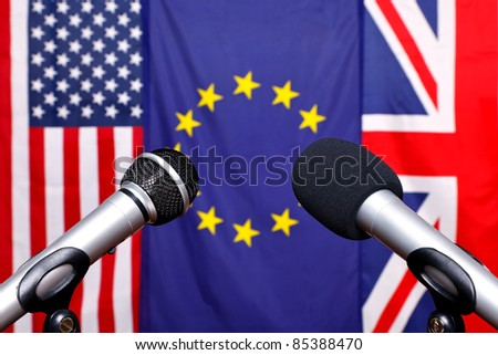 Two microphones on the stage of a press conference with the flags from America, European Union and the United Kingdom in the background.