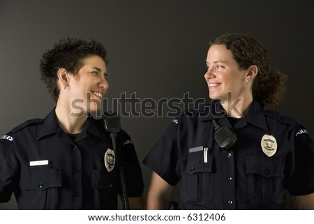 Two mid adult Caucasian policewomen standing looking at each other smiling.