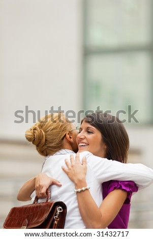 two mid adult colleagues hugging outdoors. Copy space