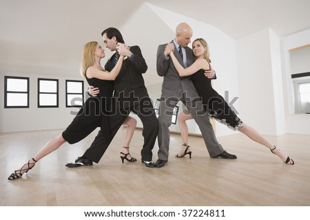 Two mid adult couples dancing Argentine Tango