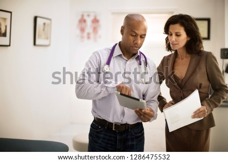 Two mid adult doctors looking at a digital tablet together.