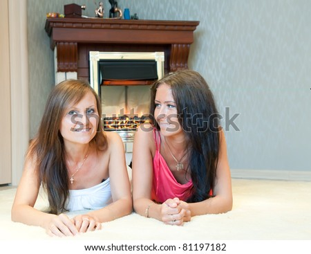 Two mid adult women near the fireplace