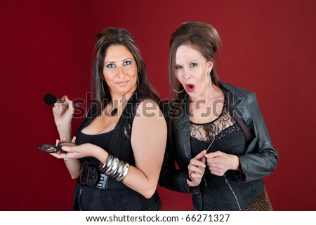 Two middle-aged ladies dressed in black prepare their makeup
