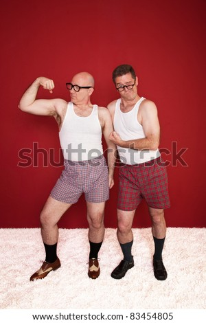 Two middle-aged men in boxers flex their muscles