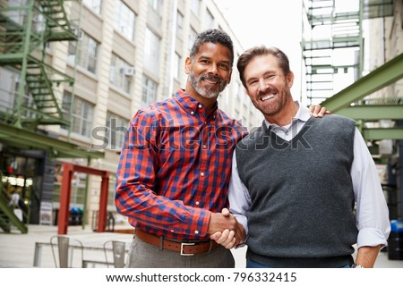 Two middle aged men shaking hands outside their workplace #796332415