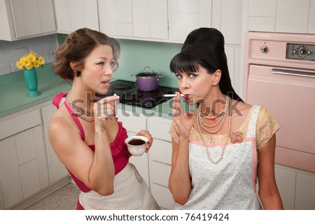 Two middle-aged retro styled women smoking cigarettes and having coffee