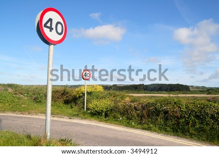 Two 40 miles an hour signs on a country lane.