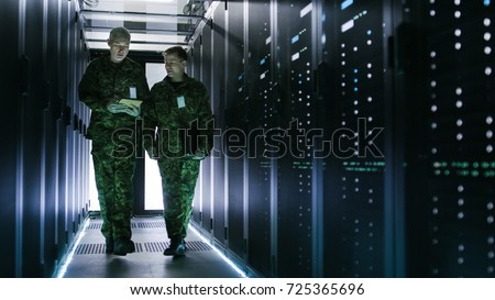 Two Military Men Walking in Data Center Corridor. One Uses Tablet Computer, They Have Discussion. Rows of Working Data Servers by their Sides.