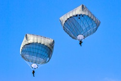 Two military paratroopers parachutes in the sky