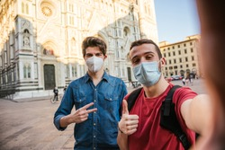 Two millennial tourist men friends taking a selfie in front of Florence cathedral with the smartphone wearing face mask in protection by infection from Coronavirus, Covid-19