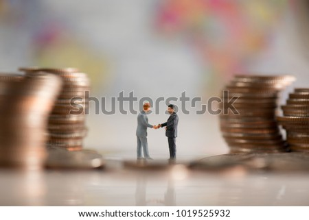two miniature businessmen make an agreement in the group of the coin stack with background is world map illustrate financial, business, agreement concept #1019525932