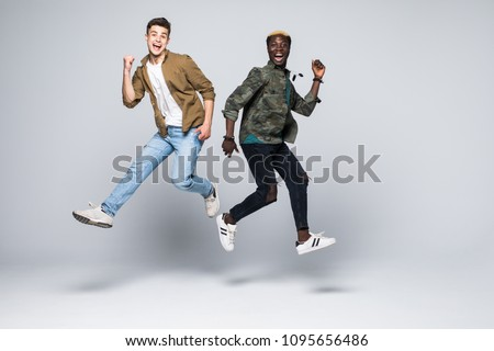 Two mixed race friends student jumping isolated on white background.
