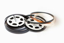 Two 8mm film reels with film strips scattered around. Studio shot. Close-up image isolated on white background.