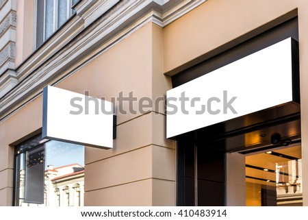 Two mock ups of restaurant white  modern rectangular street signboards on yellow wall