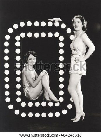 Two models posing by large letter O