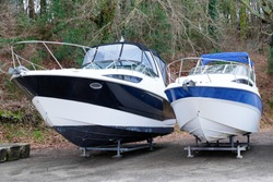 two modern boats yachts stored up in dry boat storage waiting for maintenance