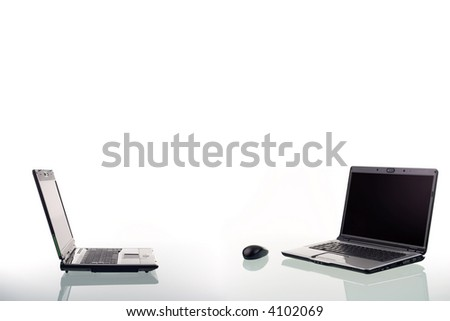 Two modern laptop computers and wireless mouse with reflection on a glass surface.