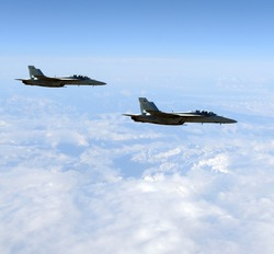 Two modern military jet fighters above mountain tops