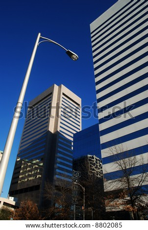 Two modern office buildings with a modern street light appearing to arch over one of them.