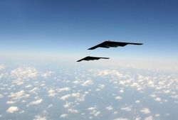 Two modern stealth bombers flying at high speed