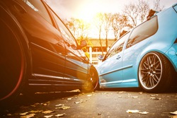 Two modified low cars in brown and light blue color. Stance custom cars with a forged polished wheels parked on a street at sunny day. Tuned automobiles