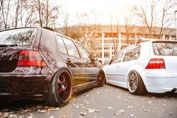 Two modified low cars in brown and light blue color. Stance custom cars with a forged polished wheels parked on a street at sunny day. Tuned automobiles with air suspension