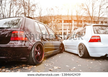 Two modified low cars in brown and light blue color. Stance custom cars with a forged polished wheels parked on a street at sunny day. Tuned automobiles with air suspension #1384642439