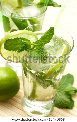 Two mojito cocktails with lime, mint leaves and ice on wooden placemat background - stock photo
