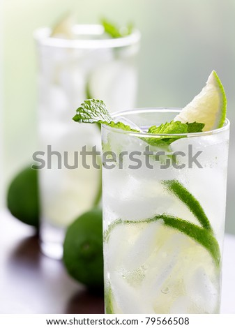 two mojitos closeup with selective focus on mint leaf