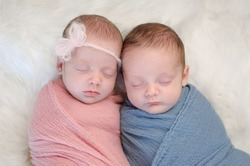 Two month old, fraternal twin, brother and sister babies swaddled in pink and blue wraps and sleeping on a sheepskin rug.