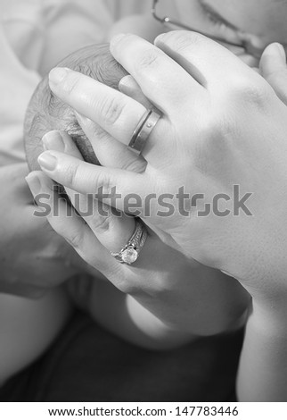 Two mother's hands holding a newborn baby - stock photo