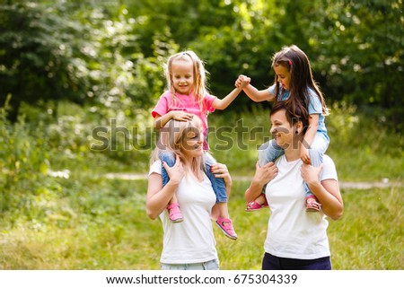 Two mothers and two small daughters in the park #675304339