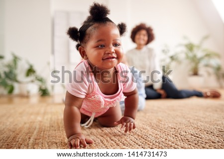 Photo of  Two Mothers Meeting For Play Date With Babies At Home In Loft Apartment