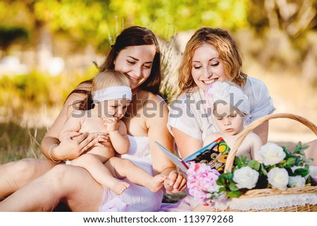 Two mothers with their children outdoor in summer park