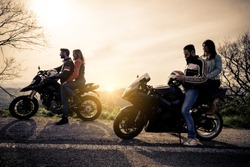 Two motorbikes driving in the nature - Friends driving racing motorcycles with their girlfriends - Group of bikers stop in a panoramic view point and look at suggestive sunset