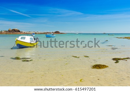 Two motorboats anchored at the seashore above yellow sand, copy space, background texture, Channel Islands, Jersey, near Le Hocq Tower