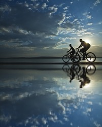 two mountain biker silhouette in sunrise with reflection in blue water