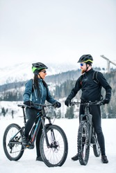 Two mountain bikers with bicycles resting outdoors in winter.
