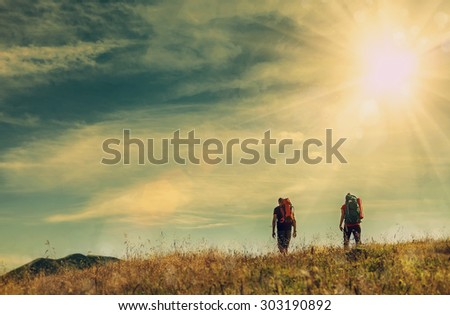 Two mountain travelers with backpacks under blue sky
