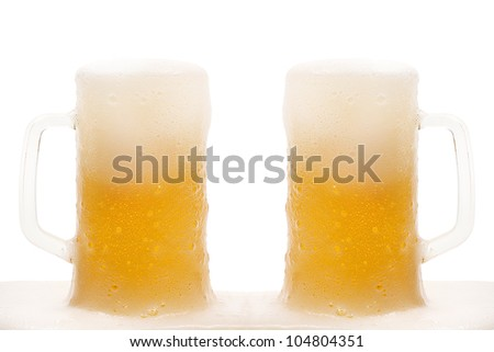 Two mug of beer with froth isolated - stock photo